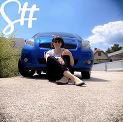 Frau sitzt am Boden vor blauem Auto und lächelt