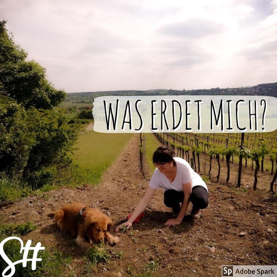 Frau mit Hund kniet am Weinberg