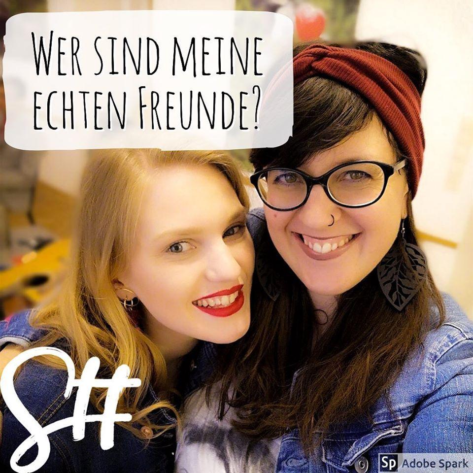 Eine blonde und eine dunkelhaarige Frau lächeln