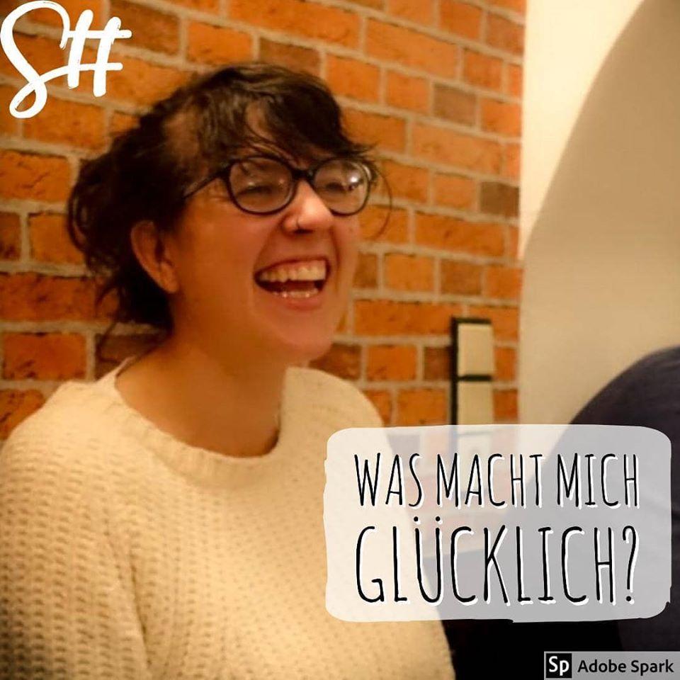 Frau mit Brille in weißem Pullover lacht herzhaft
