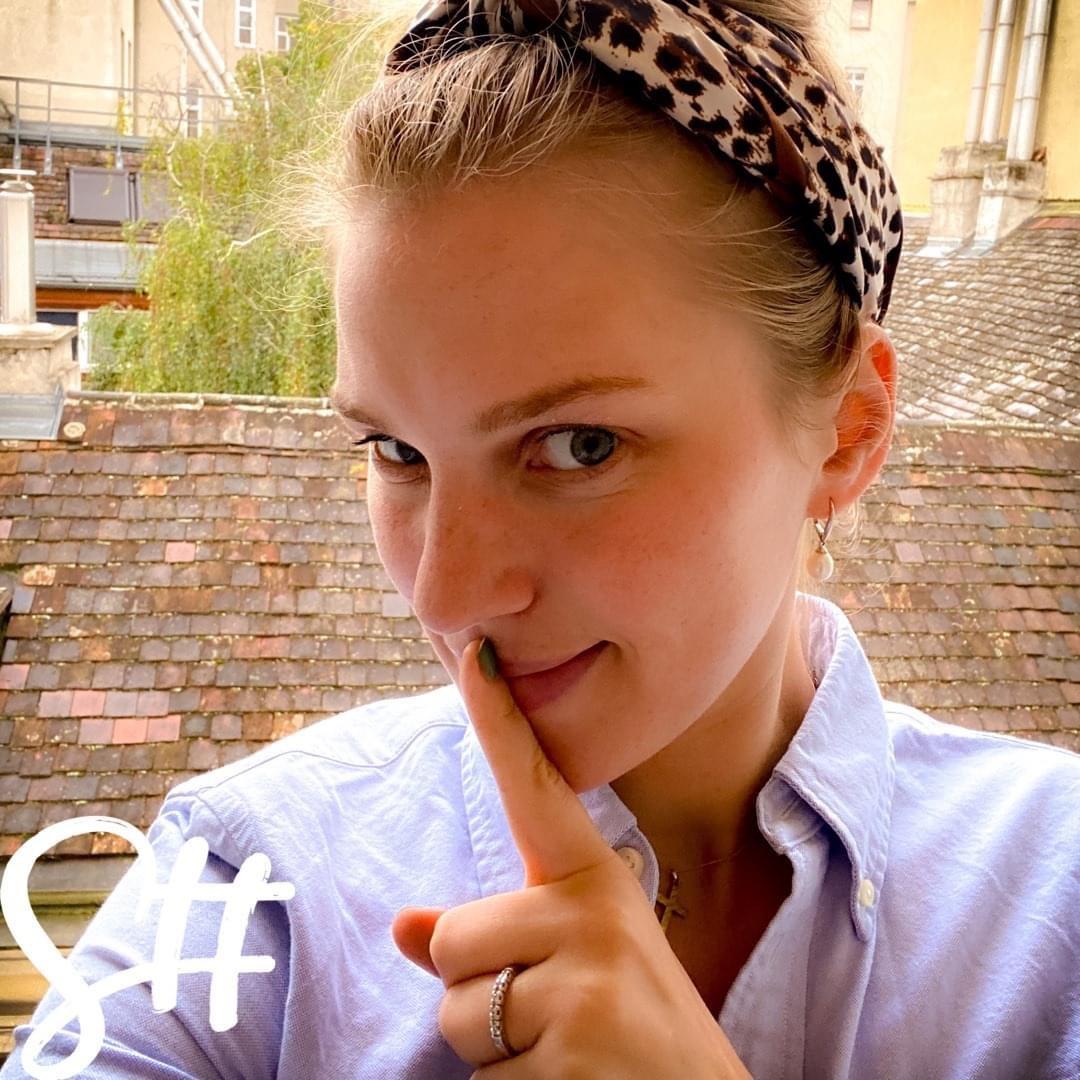 Frau macht mit dem Finger das Schweigesymbol